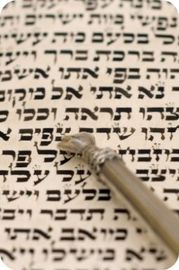 "a silver ""yad"" pointer on a page from the torah, the first five books of the hebrew bible.  selective focus, shallow depth of field."
